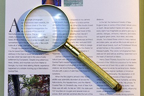 Open book with a magnifying glass laying on top